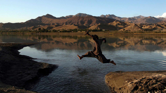An Afghan boy jumps to cross a stream in Surabhi, some 100 kms from Kabul, Afghanistan, 2009.