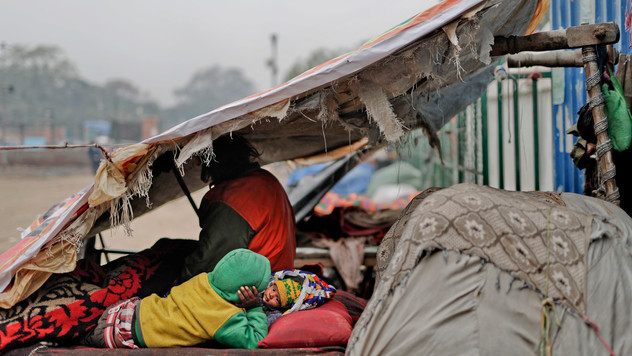 7-year-old Farmaan, back to camera, lies next to his three-month-old sister Razia on a wooden fruit vendor's cart, which is his home, as they wake up on a cold morning in New Delhi, India.