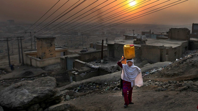 An Afghan girl carries water in a plastic container as she ascends a slope on the way towards her house in Kabul, Afghanistan, 2010.