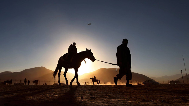 Afghan boys enjoy a joy ride on a horse back during the final sunset of the year in Kabul, Afghanistan, 2010.