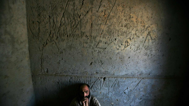 Mujahid, an Afghan opium addict, who has lost his mental balance, sits inside his cell as he is chained to the wall at the Mia Ali Baba Shrine, on the outskirts of Jalalabad, Afghanistan, 2009.