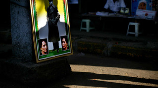 Shadow of a pedestrian falls on the framed photograph of Myanmar's democracy icon Aung San Suu Kyi and her late father Gen. Aung San as it is placed on a sidewalk for sale at a market place in Yangon, Myanmar, 2012.