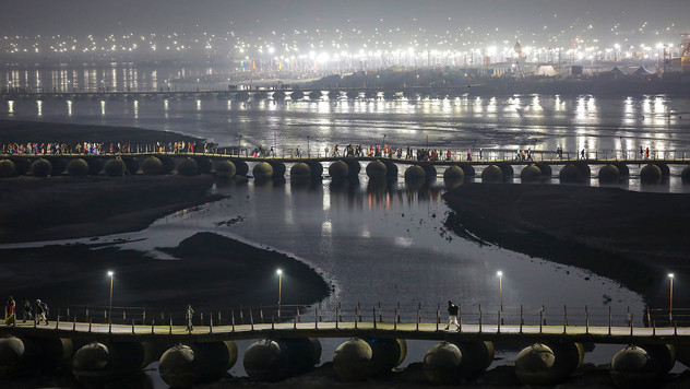 Indian Hindu pilgrims walk on a pontoon bridge before dawn at Sangam, the confluence of rivers Ganges, Yamuna, and mythical Saraswati during Magh Mela, a festival that attracts millions of pilgrims every year, in Prayagraj, in the northern Indian state of Uttar Pradesh, Thursday, Jan. 30, 2020. In the run-up to the bathing festivals, extra water is released upstream and tanneries are temporarily closed to temporarily clean up the waters of the Ganges.But pollution officials say that it is unsafe to bathe in the Ganges anywhere near Prayagraj. To Hindus, however, the river remains pure in a religious sense.