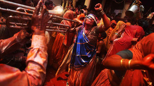 An elderly Indian Hindu woman dances on the tunes of a band during Holi celebrations, the Hindu festival of colors, at the Dauji Temple in Dauji, Uttar Pradesh state, India. The Dauji Temple festivities are known for a ritual where the women playfully hit men with whips made of cloth as men throw buckets of water with orange dye.