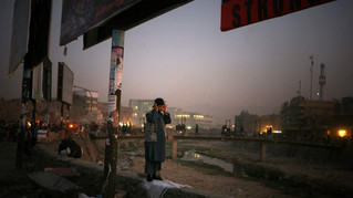 Afghan men offer evening prayers on the parapet of a canal at a market place in Kabul, Afghanistan, 2009.