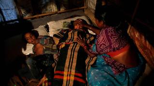 Marjina tends to her sick daughter Murshida, 12, as her son Shahid-ul, 7, lies beside, inside their rented shanty, Oct. 2014.
