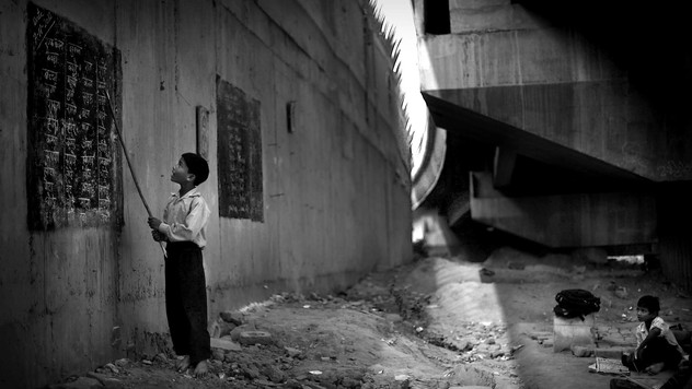 Underprivileged Indian child Rajesh, 8, reads from a black board, painted on a building wall, at a free school run under a metro bridge in New Delhi, India, Wednesday, Nov. 7, 2012.