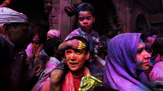 A Hindu man, carrying his son on his shoulders, negotiates his way through a crowd inside the Banke Bihari temple on the holi festival in Vrindavan.