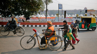 the Khan family, led by Nisar Khan, make their way to a temple to receive donations and free food in New Delhi, India.
