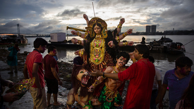 Indian Hindu devotees prepare to immerse an idol of goddess Durga in the river Hooghly, a distributary of the river Ganges, in Kolkata in the eastern Indian state of West Bengal, Oct. 9, 2019. Hundreds of thousands of idols are immersed into the Ganges and other rivers across the country on Durga Puja festival, causing serious concerns of environmental pollution. The Hooghly is also known as the Ganga river by locals.