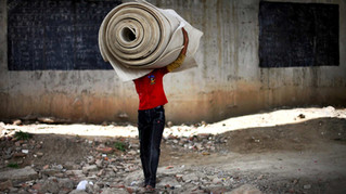 An underprivileged boy carries the flooring, which was donated by a philanthropist, for storage till next morning at a temporary storeroom as class ends at a free school run under a metro bridge in New Delhi, India, Mar. 13, 2013.