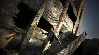 An Afghan opium addict comes out of the bombed-out ruins of the former Russian Cultural Center, in Kabul.