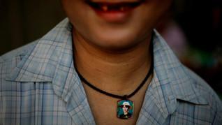 A Myanmar man wears a locket holding the photograph of Myanmar's democracy icon Aung San Suu Kyi in Yangon, Myanmar, 2012.