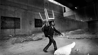 An underprivileged Indian boy tries to lift a sack containing mats while carrying plastic chairs on his head to store them till next morning at a temporary storeroom as class ends at a free school run under a metro bridge in New Delhi, India, Tuesday, Dec. 11, 2012.