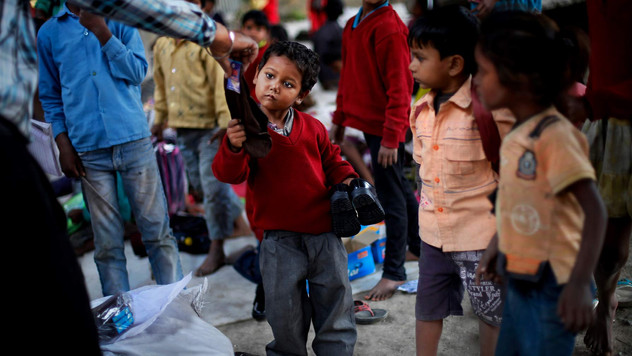 Shivam, an underprivileged child, receives new pair of socks and shoes donated by a philanthropist, at free school run under a metro bridge in New Delhi, India, Mar. 19, 2013.