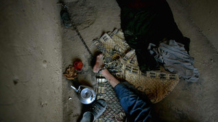 Rafi, an Afghan opium addict, who has lost his mental balance, is chained to the wall at the Mia Ali Baba Shrine, on the outskirts of Jalalabad, east of Kabul, Afghanistan, 2009.