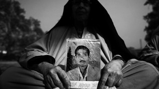 Mughli, an elderly Kashmiri woman, holds the photograph of her disappeared son, Nazir Ahmad Teli, during a monthly protest demonstration against involuntary disappearances at a public park in Srinagar, the summer capital of Indian-administered Kashmir, Nov. 10, 2007.