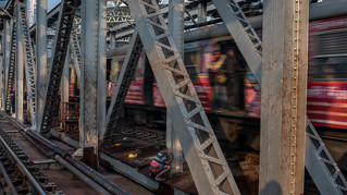 A passenger train passes by as an Indian man defecates on a railway bridge over Buri Ganga, a tributary of River Hoogly in Kolkata, in the eastern Indian state of West Bengal.
