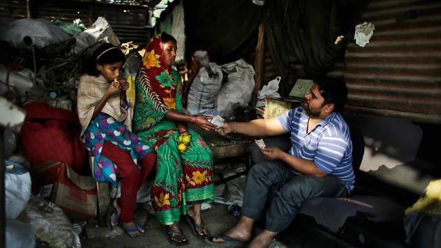 Munna bhai, a trash dealer, hands over money to Marjina for trash she segregated, as her daughter Murshida eats sweet lemon.