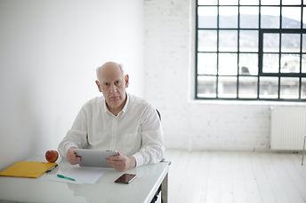 older man working at desk.jpg