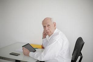 older man looking up from desk.jpeg