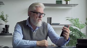 older man staring at phone.jpg