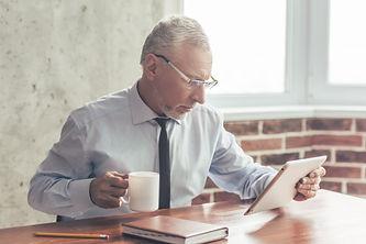 older man at desk with coffee.jpg