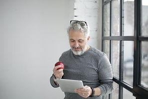 older man lookinig at tablet.jpeg