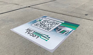 Photo showing QR code decal on a sidewalk