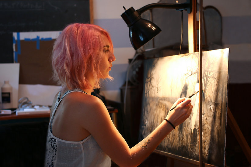 artist with pink hair painting on an easel
