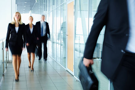 Stock image of businesspeople walking down a corridor.