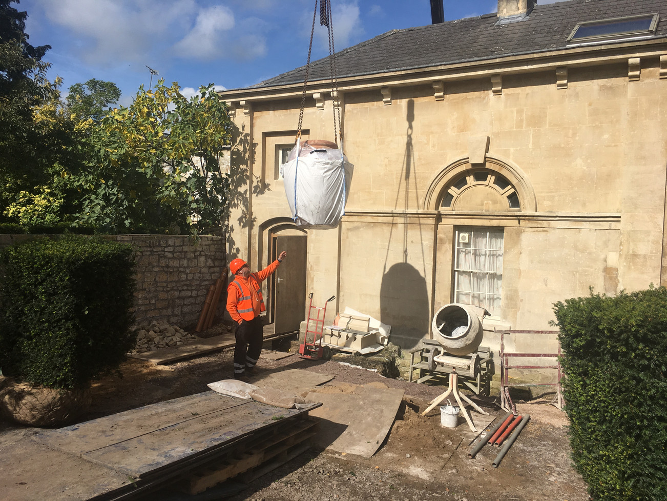 arrival of large terracotta oil jar by crane