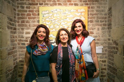 Participating artist Mariam Ali Fakhro in front of her work with guests