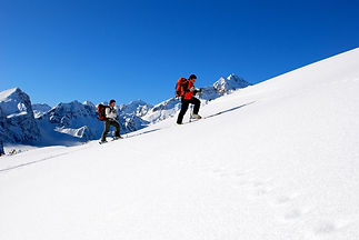 Two ski tourers on an ascent through a snowy landscape in Switzerland