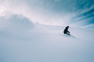 Freerider on a snowboard leaves a big cloud of snow