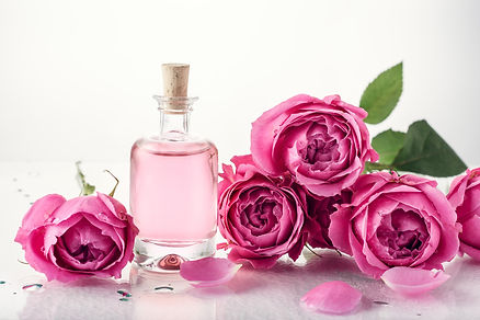 Roses, pink perfume essence in a bottle.