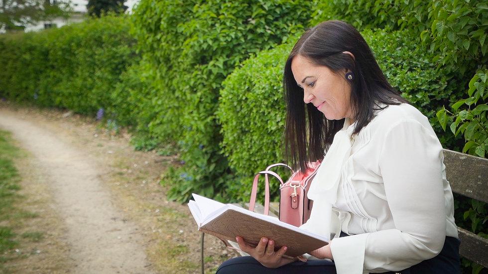 Jenny McDonald reading on a bench