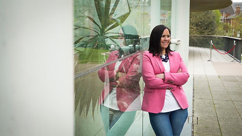 Jenny McDonald Smiling. Leaning against glass with reflection. Welcome Page