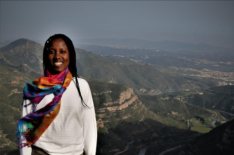 Black African girl at mountain ledge in