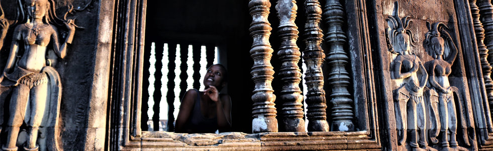 African girl looking through Angkor Wat
