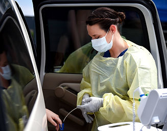 Medical professional in scrubs wearing a mask, administering a pulse oximeter test to someone in a car