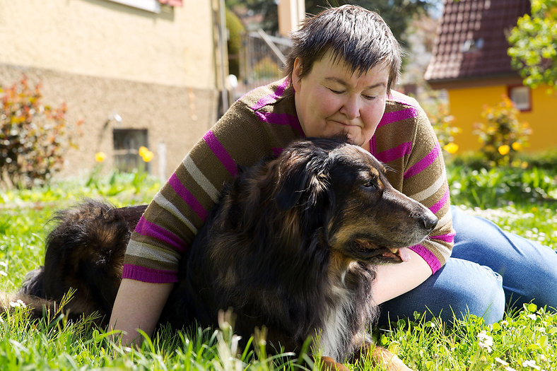 Person sitting on grass hugging their dog.