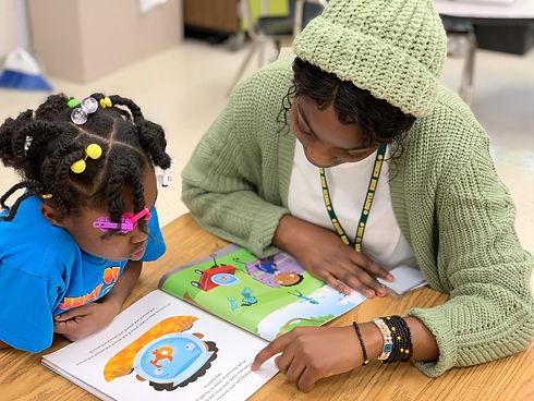 Black women reading with black student.j