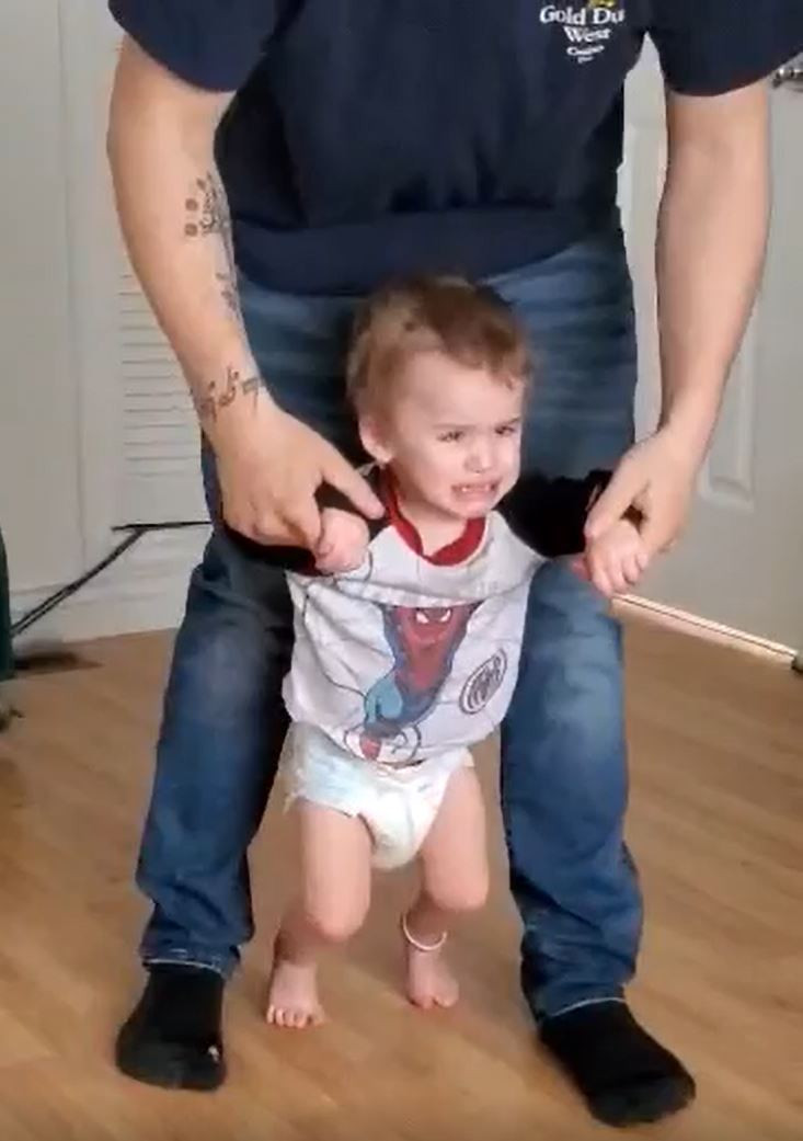 Boy in t-shirt and diaper walks, unhappy face, his dad holds both his hands from behind.