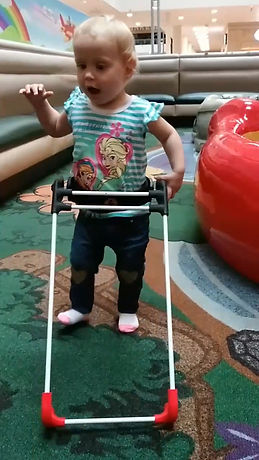 one year old girl walking with belt cane.