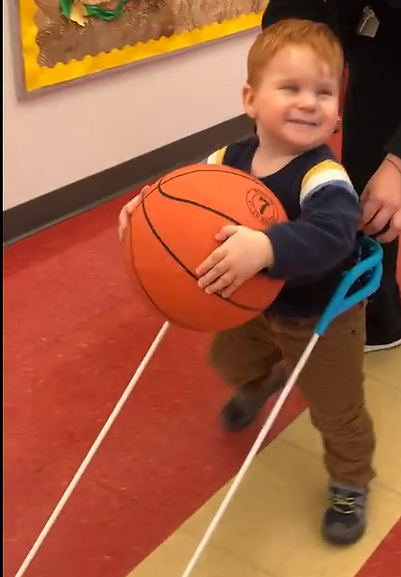 two-year-old boy, CHARGE syndrome, wearing belt cane holding a basket ball walking independently for the first time