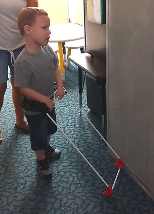 Three year old boy holds belt cane with both hands, cane base contacts the file cabinet in front of him.