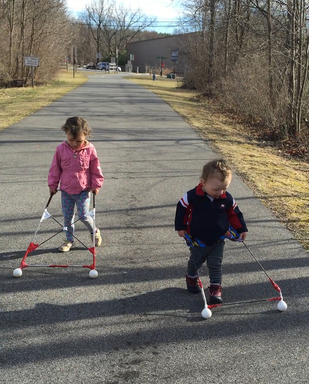 Two children under five are walking on an outdoor walking path. Lily is pushing a rectangular cane with black, white and red tape and rolling tips. Logan is wearing the belt cane described in this article.