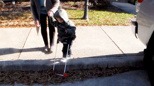 Wearing his cane, the base of the frame has fallen off the curb ahead of Student M.
