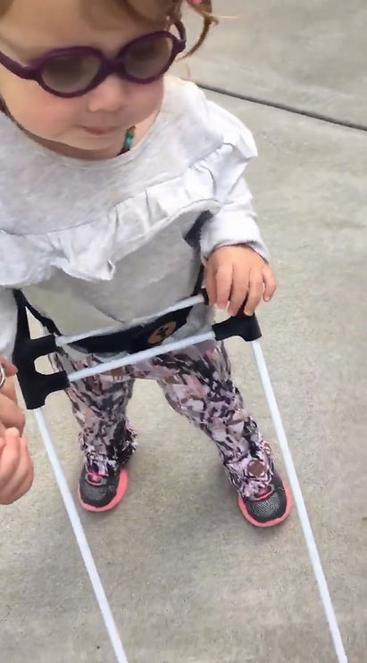 one-year-old girl who is visually impaired wears belt cane